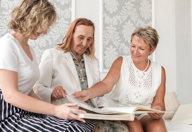 Multi generation women looking old photo album during sitting on sofa Free Photo