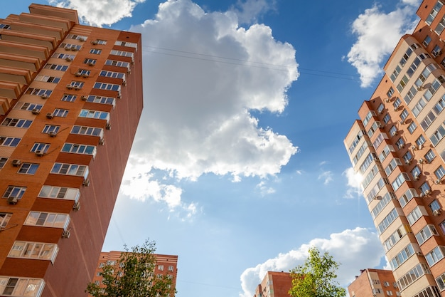 Multi-storey panel house bottom-up view through the crowns of trees. white clouds and blue sky are visible. there is a place for text. Premium Photo