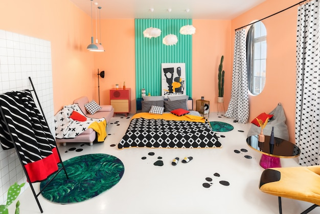 Multicolor bedroom with geometrical patterns in interior and textile. Premium Photo