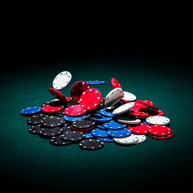 Multicolor casino chips on green poker table Free Photo