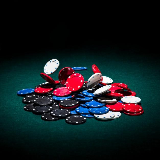 Многоцветные фишки казино на зеленом покерном столе Premium Фотографии
