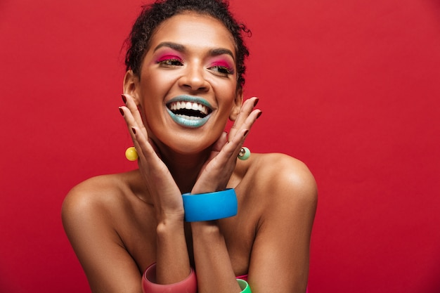 Multicolor cheerful african american woman with fashion makeup smiling and looking aside, isolated over red wall Free Photo