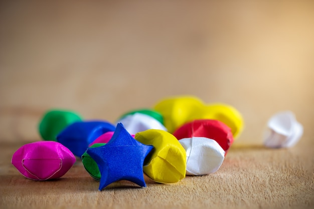 Multicolor paper star laid on wooden table with morning sunlight. Premium Photo