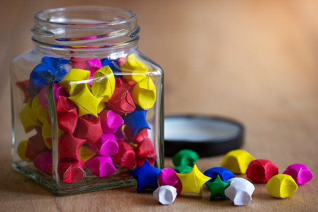 Multicolor paper star in square glass bottle on wooden table with morning sunlight. Premium Photo