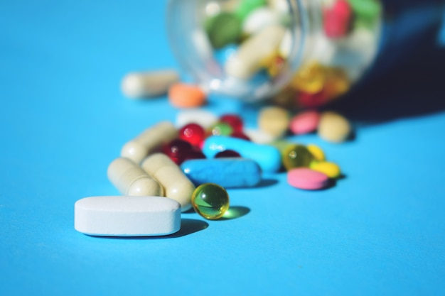 Multicolor tablets and pills capsules from glass bottle on blue Premium Photo