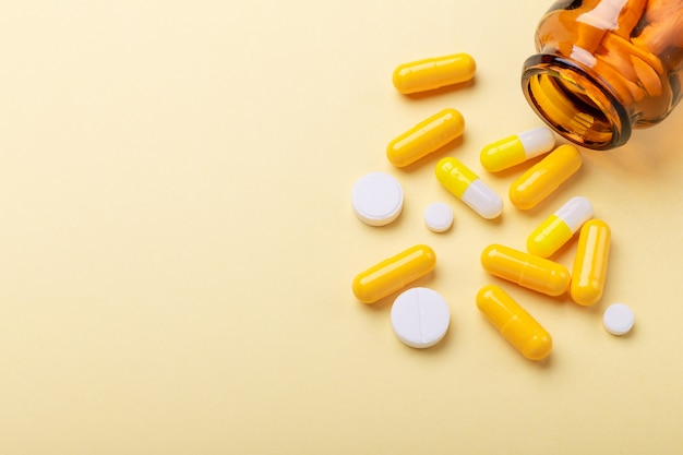Multicolor tablets and pills capsules from glass bottle on yellow Premium Photo