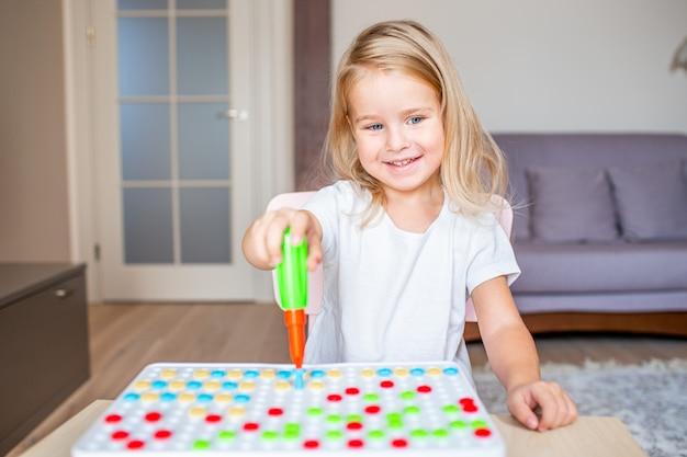 Маленькая белокурая девушка сидя на таблице дома играя с отверткой игрушки и multicolor винтами. раннее образование. Premium Фотографии