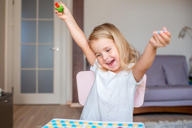 Счастливая милая маленькая белокурая девушка сидя на таблице дома играя с отверткой игрушки и multicolor винтами. раннее образование. Premium Фотографии