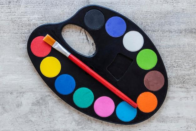 Tavolozza del vassoio dell'artista multicolore su fondo di legno Foto Gratuite