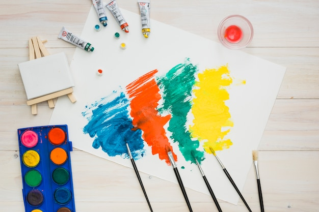 Multicolored brushstroke on white page with painting equipment on wooden table Free Photo