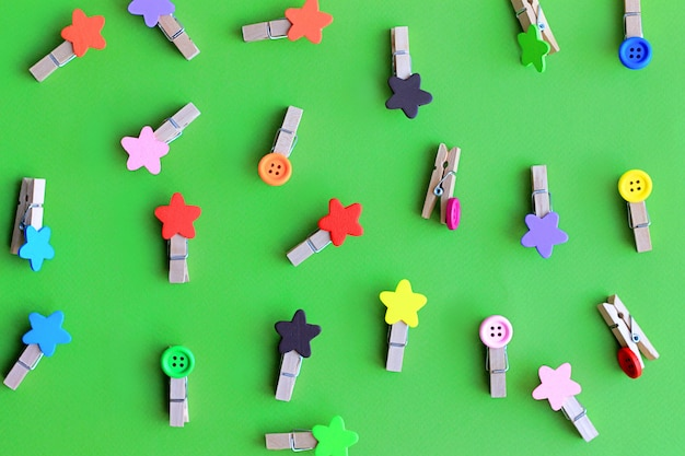 Multicolored decorative clothes pegs for clothes on green background pattern Premium Photo