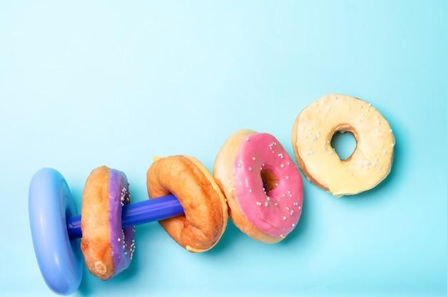 밝은 파란색 표면에 여러 가지 빛깔 된 도넛 프리미엄 사진