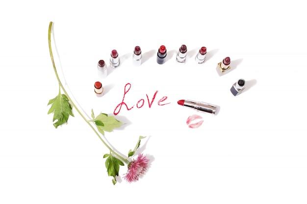 孤立した背景に色とりどりの光沢のある口紅。白い表面に野生の紫色の花。唇は紙にキスします。赤い唇の鉛筆の跡 Premium写真