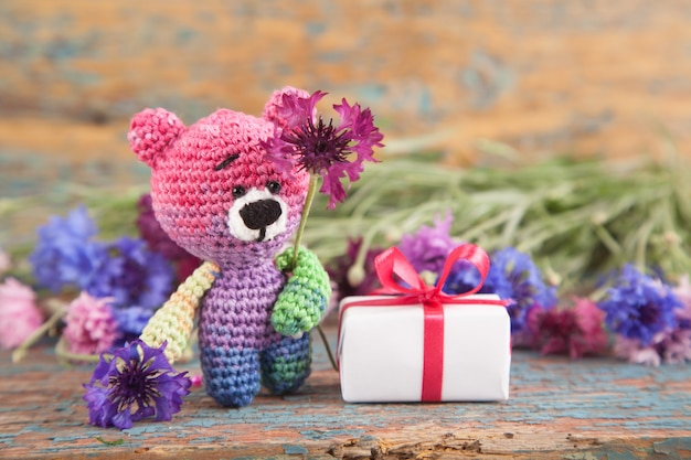 Multicolored knitted small bear with cornflowers on an old wooden background. Premium Photo