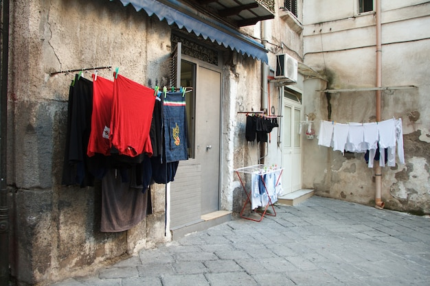 Multicolored laundered clothes are dried on the balcony in the alley of naples Premium Photo