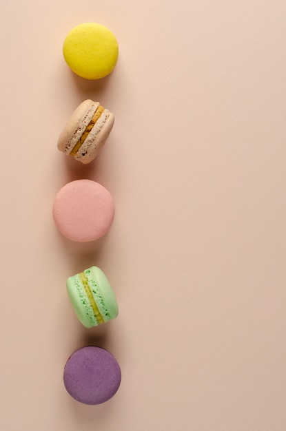 Multicolored macaroons  in a row on pastel beige. Premium Photo
