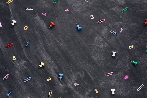 Multicolored numbers and paper clips with pushpins scattered on chalkboard Free Photo