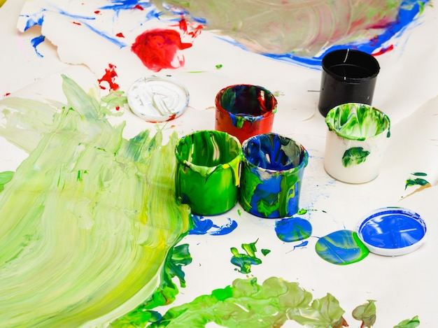 Multicolored plastic cans with paints. artist workplace background Premium Photo