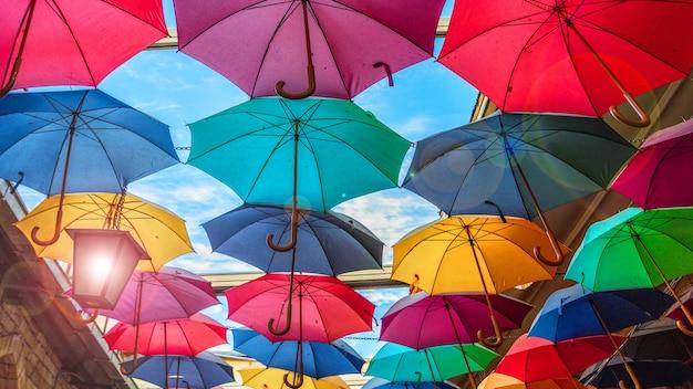 Разноцветные радуги разноцветные зонтики нависали над улицей Premium Фотографии