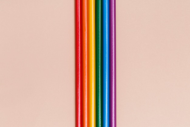 Multicolored rainbow sticks on beige background Free Photo