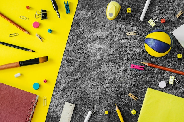 Multicolored school supplies on black and yellow blackboard background. Premium Photo