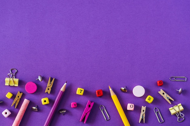 Multicolored school supplies on violet background with copy space. Premium Photo