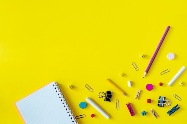 Multicolored school supplies on yellow background with copy space Premium Photo