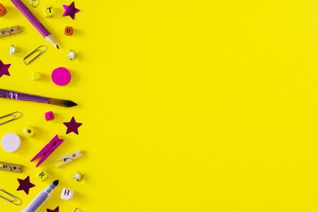 Multicolored school supplies on yellow background with copy space. Premium Photo