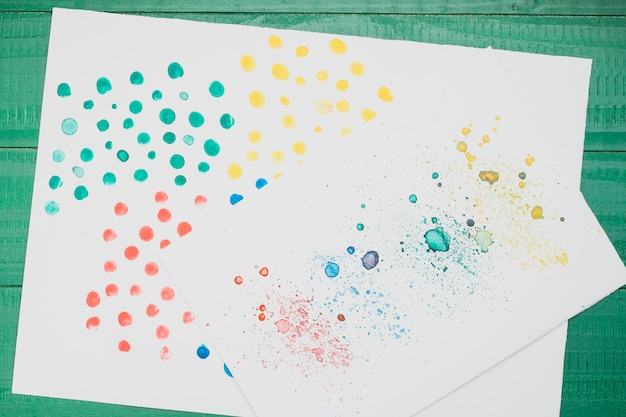 Multicolored stained abstract painting on white paper over green table Free Photo