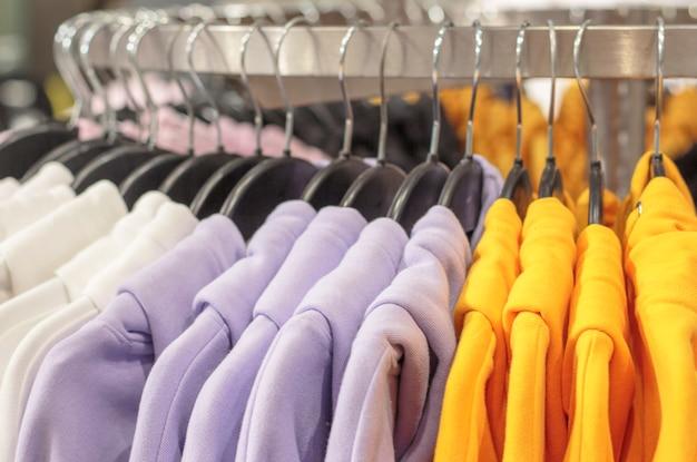 色とりどりのスウェットシャツは店のクローズアップでハンガーに掛かっています。 Premium写真