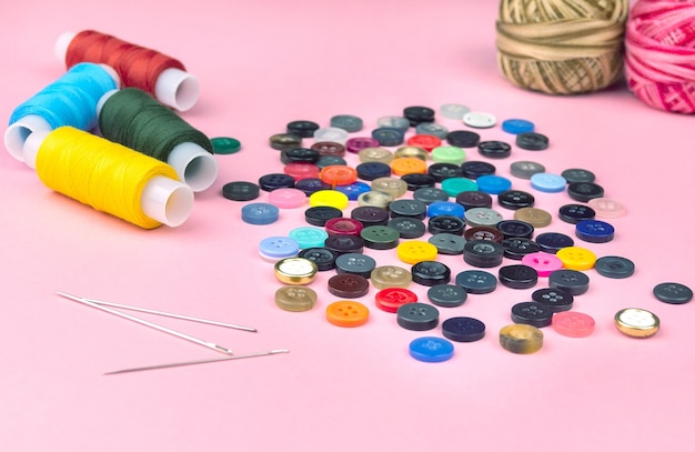 Multicolored threads and buttons on a pink background. hobby, hand background. abstract colorful background. Premium Photo