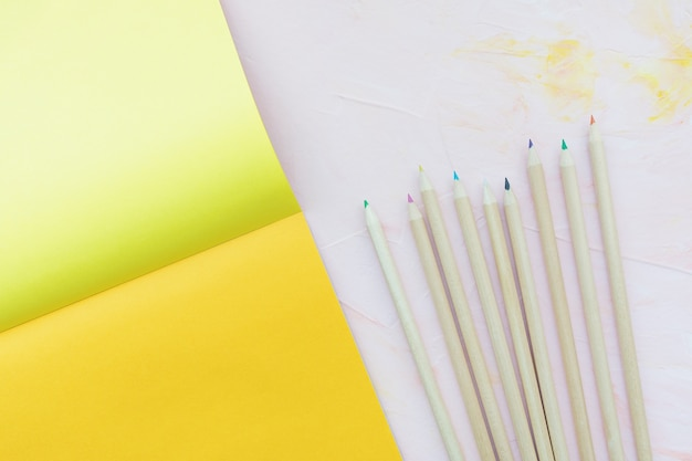 Разноцветные деревянные карандаши и листы бумаги на розовом, плоская планировка Premium Фотографии