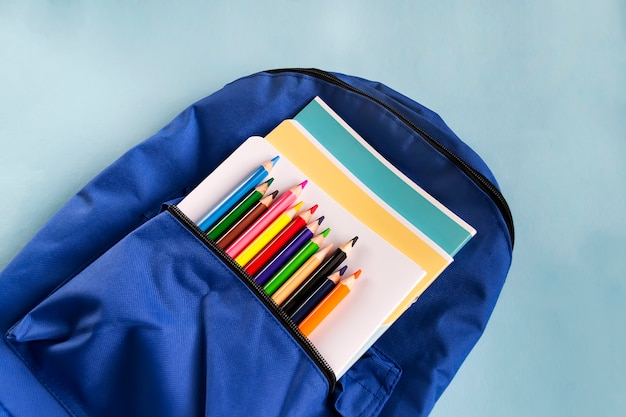 Multicolored wooden pencils and notebooks in a backpack on a paper blue background with copy space. school accessories. Premium Photo