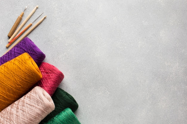 Multicoloured big sewing threads and grey copy space background Free Photo
