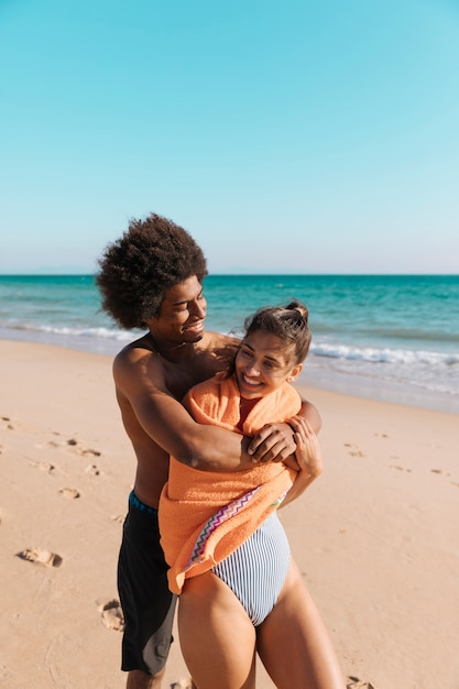 Multicultural couple having fun on beach Free Photo
