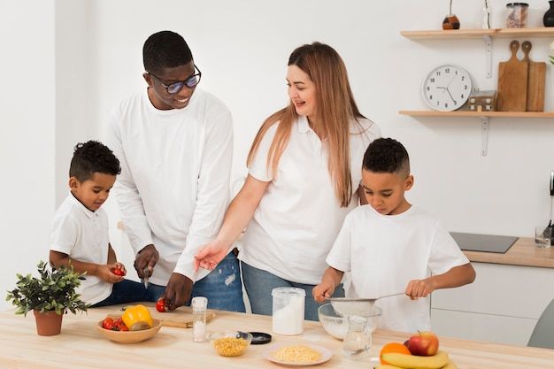 Multicultural family cooking together Free Photo