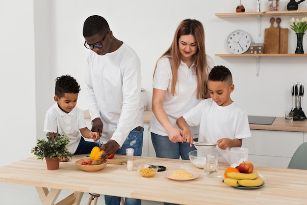 Multicultural family preparing dinner together Free Photo