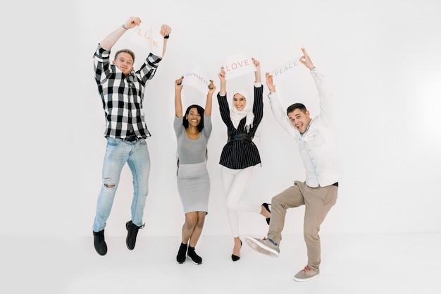 白い背景の上に一緒に立って、異なる肯定的なスローガンを保持している人々の多文化のグループ Premium写真