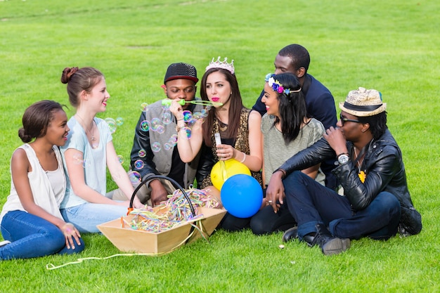 Multicultural group, sitting together on lawn Premium Photo