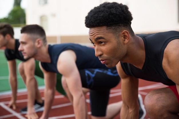 Multiethnic athlete group ready to run. focus on african man. Free Photo