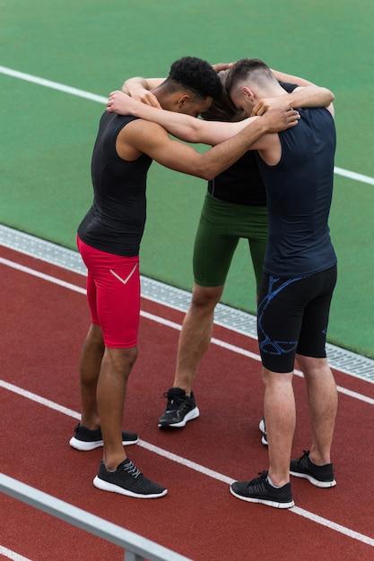 Multiethnic athlete team standing on running track outdoors Free Photo