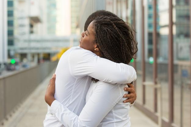 Multiethnic close friends wearing white shirts, hugging outside Free Photo