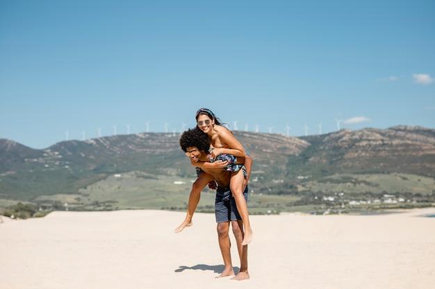 Multiethnic couple having fun on beach Free Photo