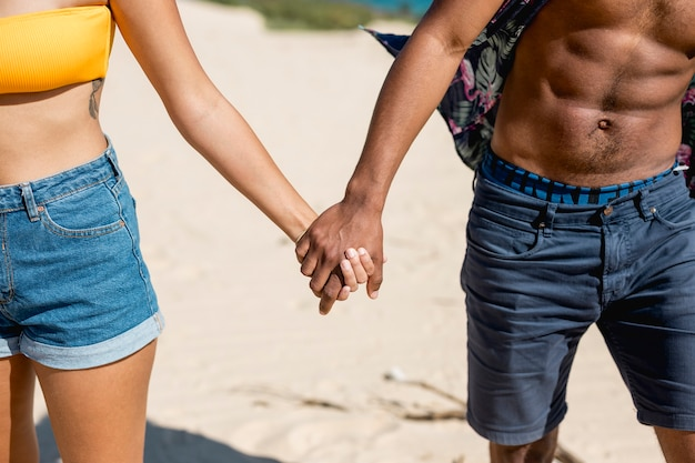 Multiethnic couple holding hands standing on sand Free Photo