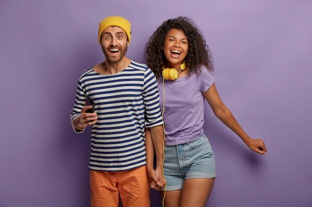 다민족 부부는 손을 모으고 즐겁게 웃으며 여가 시간을 즐깁니다. 무료 사진
