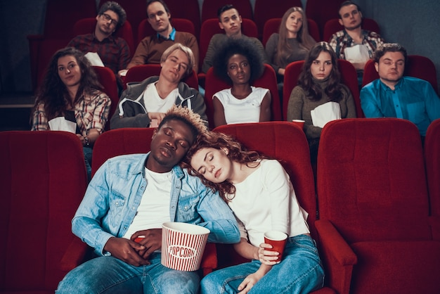 Multiethnic couple in love is sleeping in movie theater Premium Photo