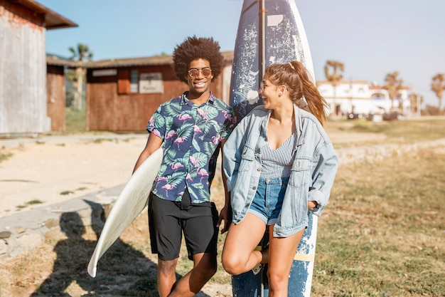 Multiethnic couple standing with surfboards Free Photo