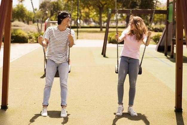 Multiethnic couple of teenagers swinging on playground Free Photo
