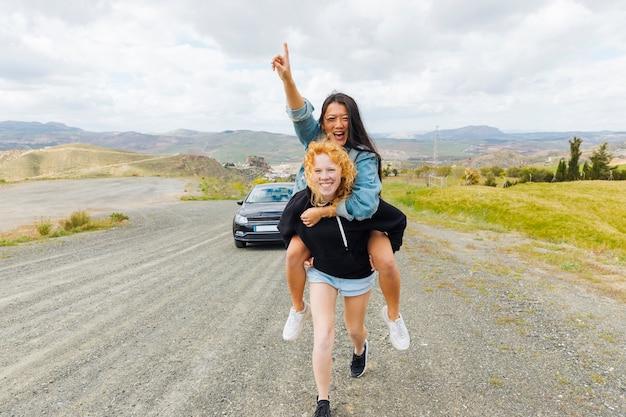 Multiethnic females playing piggyback on roadside Free Photo