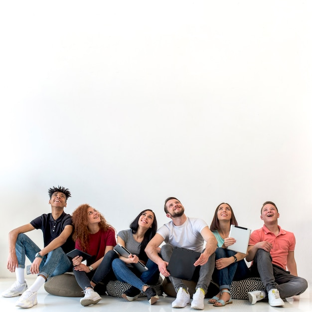 Multiethnic friends sitting on floor looking up against white backdrop Free Photo